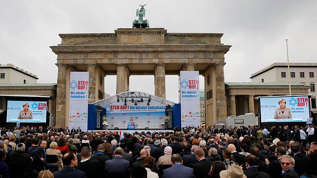 kike servent merkel rallying against antisemitism in Berlin